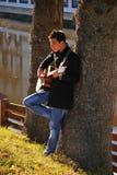 Man playing guitar under tree Stock Photo