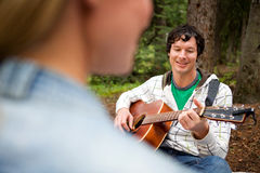 Man Playing Guitar for Woman. A man playing a guitar and singing for a woman Royalty Free Stock Photos