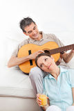 Man playing guitar for woman Stock Image