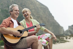 Man Playing Guitar By Woman At Beach. Middle aged men playing the guitar by a cheerful women at the beach Stock Photos