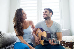 Man playing guitar for woman in bedroom Stock Photos