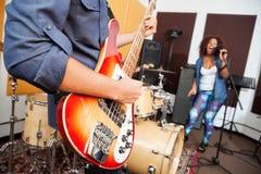 Man Playing Guitar While Woman Singing At. Midsection of men playing guitar while women singing in background at recording studio Royalty Free Stock Image