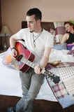 Man playing guitar while woman sitting on bed in background Stock Photos