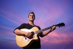 Man playing guitar. Young man playing guitar over sunset sky background Stock Photography