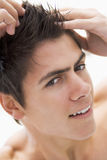 Man playing with hair smiling Stock Images