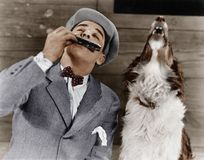 Man playing harmonica with howling dog Royalty Free Stock Photo