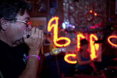 Man playing harmonica, Mississippi. A man playing the harmonica in a blues bar, Mississippi Stock Images