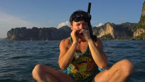 Man playing harp on kayak in the open sea water in mask and tube for diving or snorkeling. Railey Beach, Krabi, Thailand stock video footage