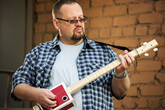 Man playing his cigar box guitar Stock Photo