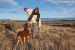 Man playing with his dog. Casual African American man playing with his dog outdoors Stock Photo