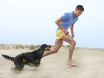 Man playing with his dog. On the beach Royalty Free Stock Photos