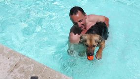 Man Playing With His Dog In The Pool. Video clip of man playing with his dog in the swimming pool stock footage