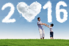 Man playing with his son in nature. Photo of young asian father playing with his son on the meadow under cloud shaped numbers 2016 and heart symbol Royalty Free Stock Photo