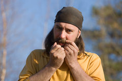 Man playing on jew's-harp. Portrait of the man playing on jew's-harp Royalty Free Stock Photo