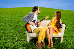 Man playing lovely song to the girl that like it on the couch. Man playing lovely song to the girl that like it on the couch on the green field Royalty Free Stock Photos