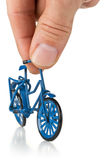Man playing with metal blue miniature bicycle Stock Image