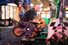 Man playing motorcycle racing arcade game. Man playing motorcycle arcade game in Niagara Falls Ontario Canada area Stock Image