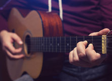 Man playing music at wooden classic guitar. Focus on fingers while holding the A chord Royalty Free Stock Photos