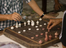 Man are playing old a chess board on wooden table.  Royalty Free Stock Photo