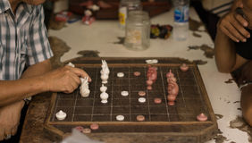 Man are playing old a chess board on wooden table.  Stock Photography