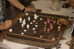 Man are playing old a chess board on wooden table.  Stock Images