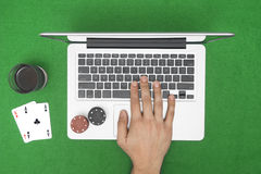 Man playing online poker with laptop on a green table with chips Royalty Free Stock Image