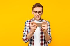 Man playing the phone on a yellow background stock image