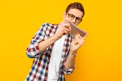 Man playing the phone on a yellow background stock photography