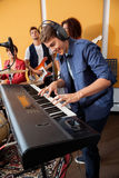 Man Playing Piano While Band Performing In. Smiling young men playing piano while band performing in recording studio Stock Photography