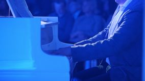 A man playing piano at the concert. Mid shot