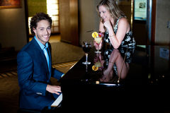 Man playing piano and entertaining his companion Royalty Free Stock Images