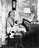 Man playing a piano with his dog next to him Royalty Free Stock Photography