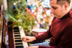 Man playing piano. At Christmas Eve royalty free stock photo