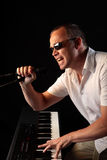 Man Playing Piano Singing into a Microphone. Male Singer playing keyboard while holding microphone on dark stage wearing sunglasses and white shirt Stock Photo