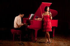 Man playing the piano and woman singing Royalty Free Stock Photography