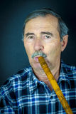 Man playing on pipe flute Stock Photos