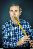 Man playing on pipe flute Royalty Free Stock Images