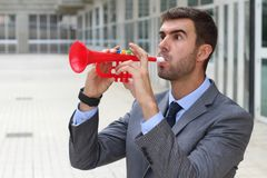 Man playing a plastic trumpet in the office Royalty Free Stock Image