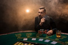 Man is playing poker with a cigar and a whiskey. A man winning all the chips on the table with thick cigarette smoke. The concept of victory Stock Photography