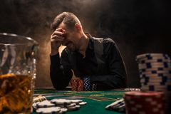 Man is playing poker with a cigar and a whiskey. A man winning all the chips on the table with thick cigarette smoke. The concept of victory. Glass with Royalty Free Stock Images