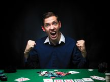 Man is playing poker. Emotional  card player win in game, man ve. Ry happy with making right choices, winning all the chips on bank. Concept of victory Royalty Free Stock Photos