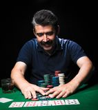 Man is playing poker. Emotional  card player win in game, man ve. Ry happy with making right choices, winning all the chips on bank. Concept of victory Stock Image