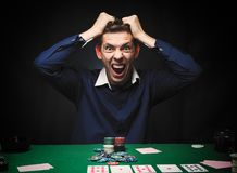 Man is playing poker. Emotional fail in game, game over for card. Player, man very angry with foolish choices, loosing all the chips on bank. Concept of victory Royalty Free Stock Images