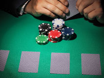 Man playing poker on green background. Royalty Free Stock Photos