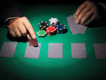Man playing poker on green background. Stock Photos