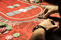 Man playing poker and looking at aces on table Stock Images