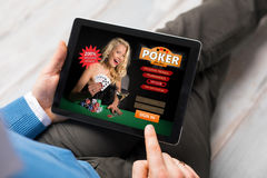 Man playing poker online. On tablet computer Stock Photos