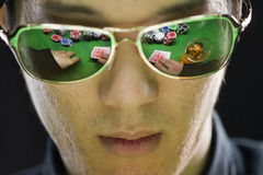 Man playing poker with reflection through his sunglasses Royalty Free Stock Photography