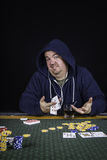 A man playing poker sitting at a table bluffing Royalty Free Stock Images