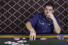 A man playing poker sitting at a table. A man sitting at a poker table gambling playing cards against a brown background Stock Images